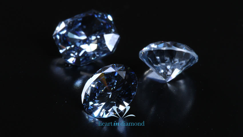 Three white cremation diamonds on a black background to remember your loved ones with the heart in diamond logo
