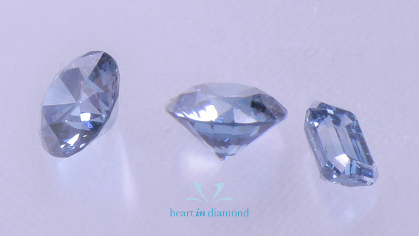 Two bluw round cut diamonds and one emerald cut cremation diamond with the heart in diamond logo