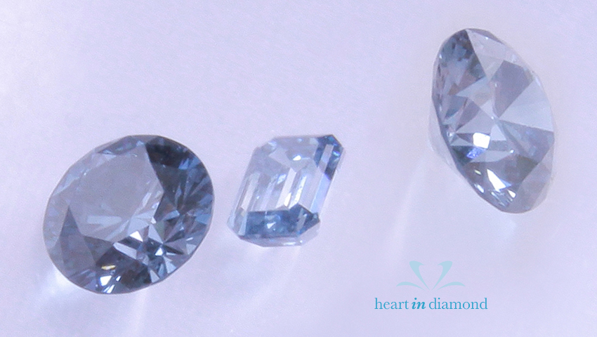 Three fancy blue cremation diamonds. Two round cut and 1 emerald cut with heart in diamond logo