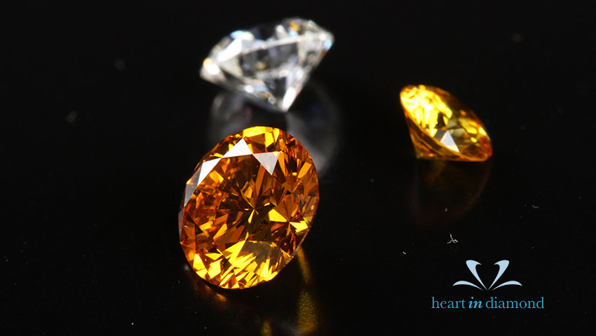 2 orange colored and 1 white diamond, all three round brilliant cut
