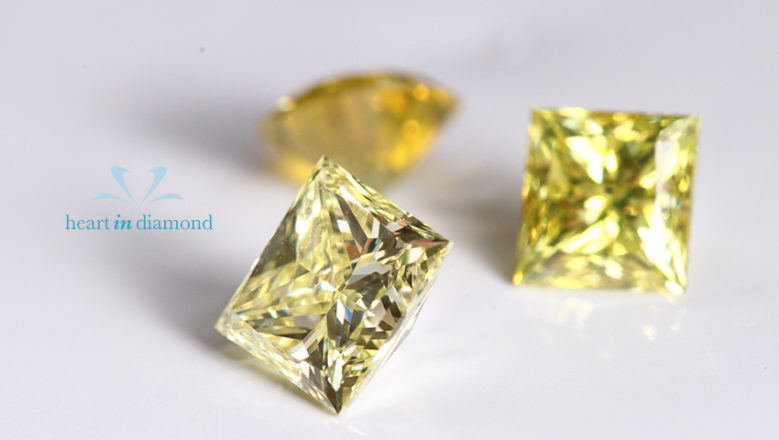 Two Princess cut yellow cremation diamonds with the logo of heart in diamond, one round cut cremation diamond in the background