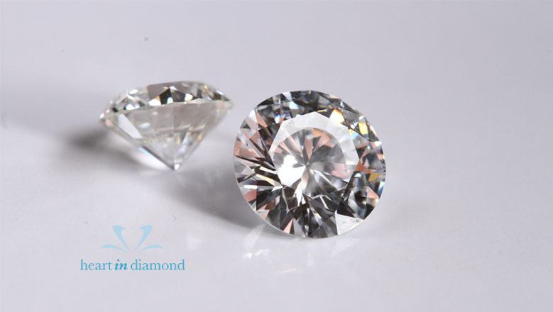 2 white round cut diamonds shown from 2 different angles with the heart in diamond logo