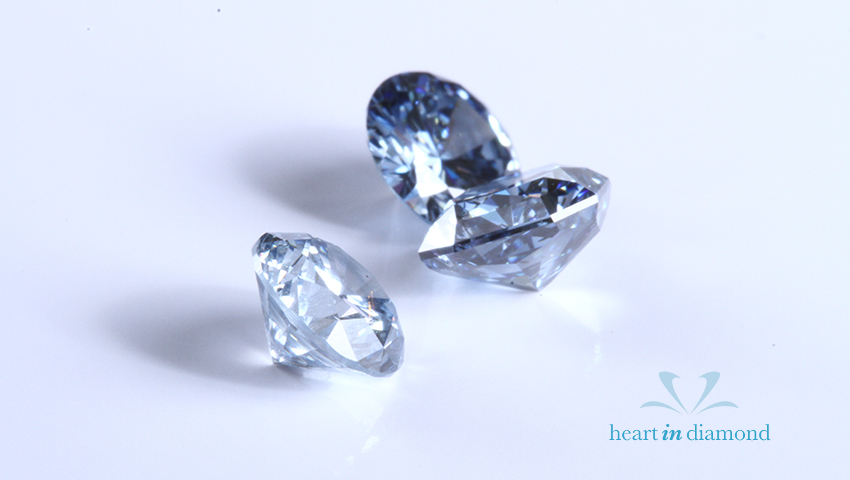 3 round brilliant cut white diamonds on a blue background