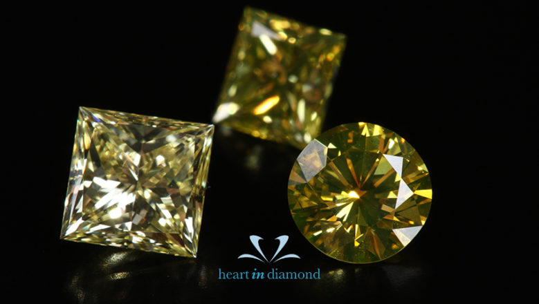 Princess cut diamonds in yellow. Two princess cut diamonds and 1 brilliant round cut diamond
