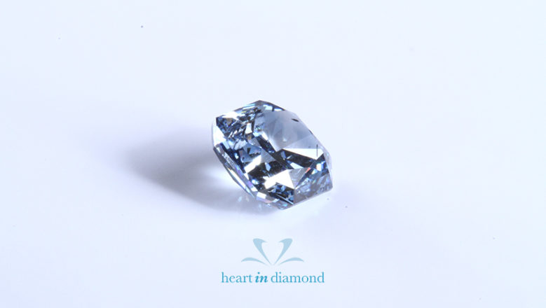 Blue radiant cut diamond made from ashes with the heart in diamond logo and a blue background