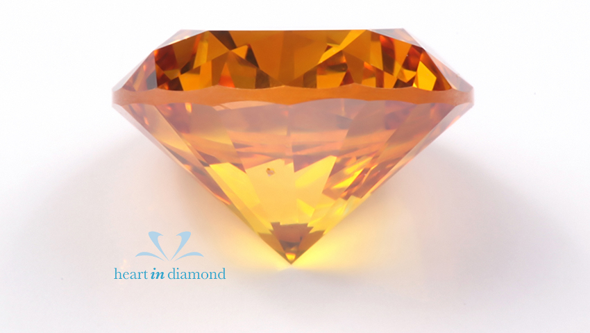 Close up of orange round cut cremation diamond with the Heart In Diamond logo