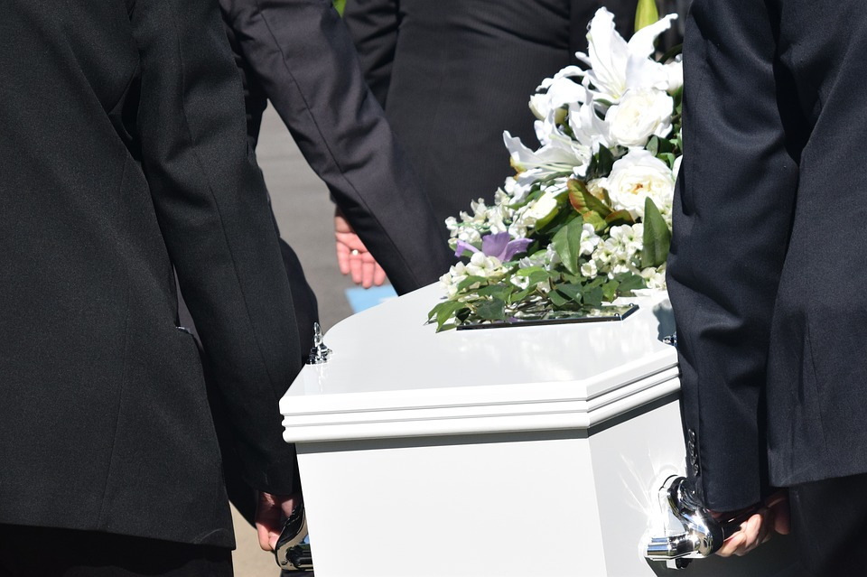 white funeral casket being carried by men
